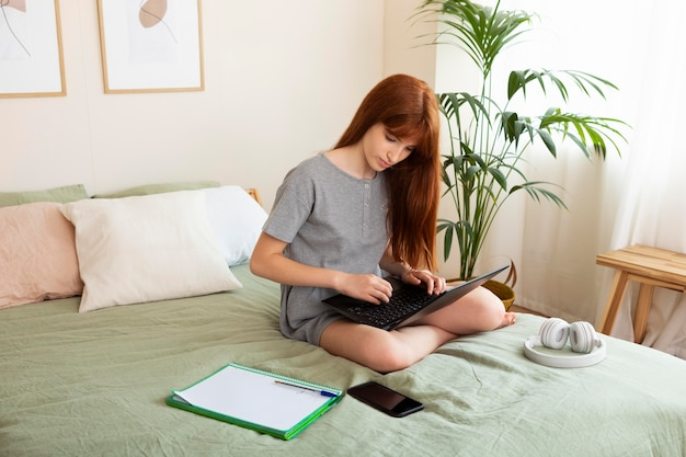 ベッドでラップトップで学ぶフルショットの女の子