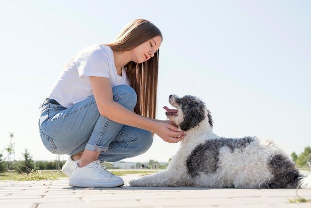 Девушка в полный рост, глядя на милую собаку