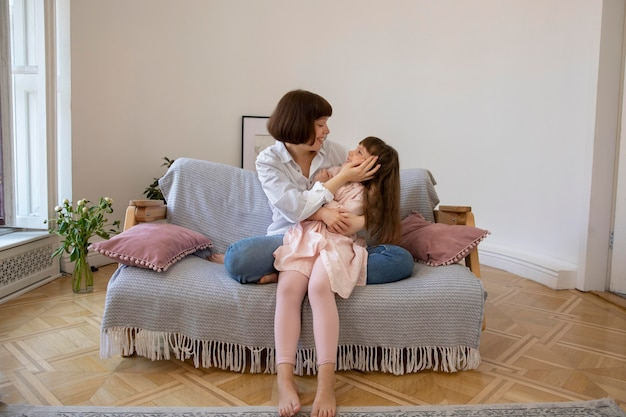 Full shot girl and mother on couch