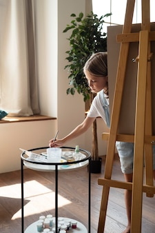 Full shot girl painting at home