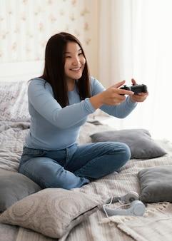 ベッドでビデオゲームをプレイするフルショットの女の子