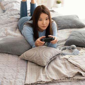 ビデオゲームをプレイするフルショットの女の子