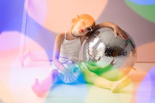 Девушка в полный рост позирует с диско-шаром и солнцезащитными очками