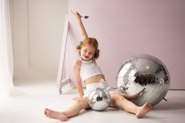 ディスコボールでポーズをとるフルショットの女の子