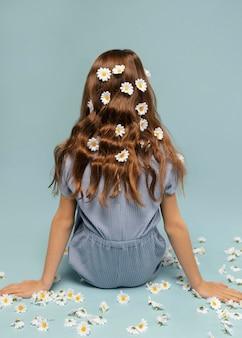 머리에 꽃과 함께 포즈를 취하는 전체 샷된 소녀
