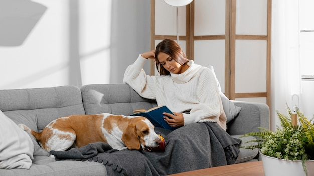 Полный выстрел девушка, читающая на диване