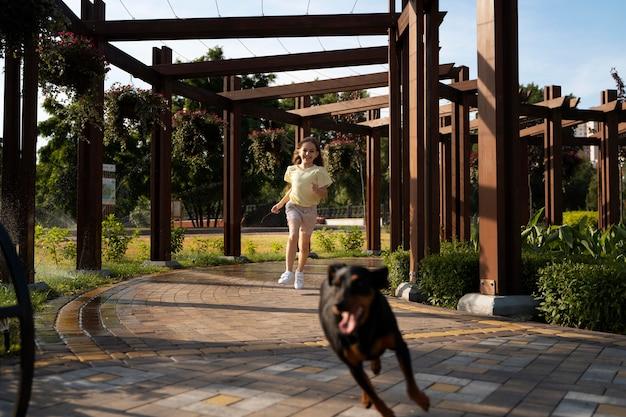 犬と一緒に走っているフルショットの女の子