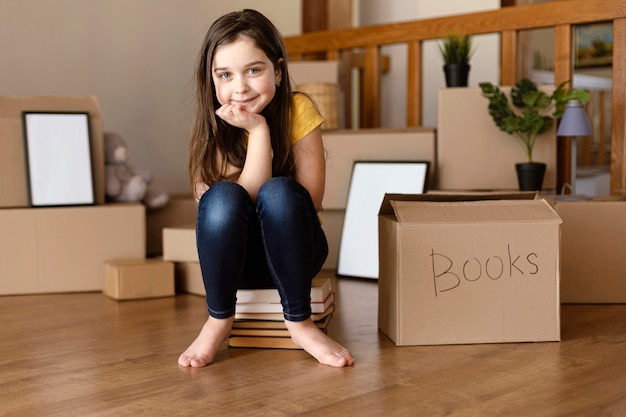 Full shot girl sitting on books