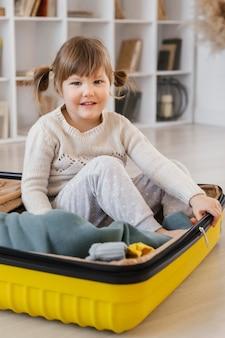 Полный снимок девушка сидит на багаже