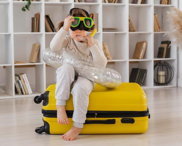 Full shot girl sitting on luggage
