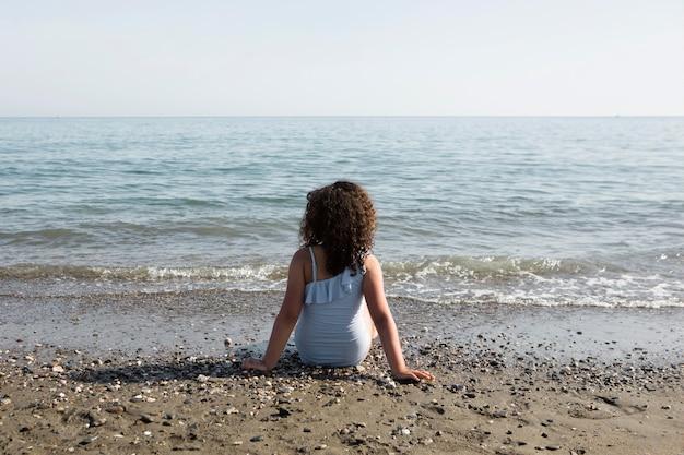 ビーチに座っているフルショットの女の子