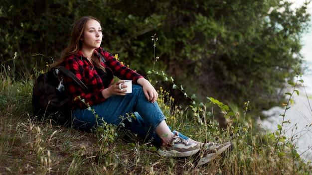 森の地面に座っているフルショットの女の子