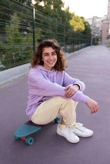 Полный снимок девушка сидит на скейтборде на открытом воздухе