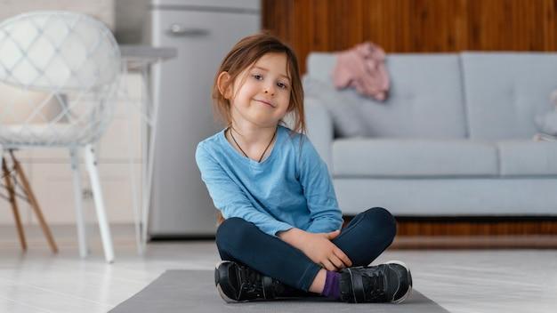 Девушка в полный рост сидит на коврике для йоги