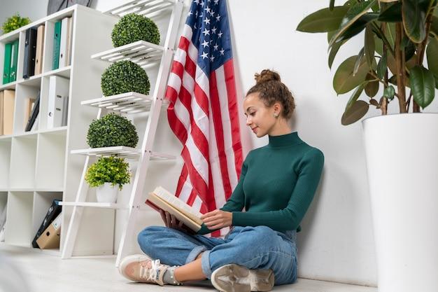 Seduta e lettura della ragazza della foto a figura intera