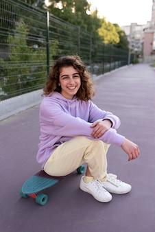 Ragazza del colpo pieno che si siede sullo skateboard all'aperto
