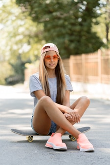 Ragazza del colpo pieno che si siede sullo skateboard