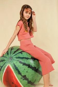 Full shot girl sitting on watermelon ball