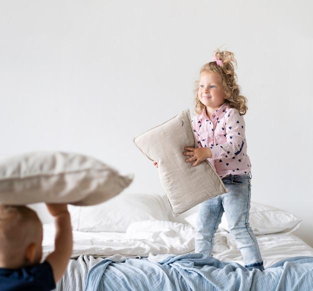 Full shot girl standing in bedroom with pillow