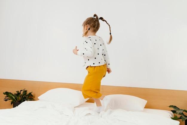 집에서 침대에 서있는 전체 샷된 소녀