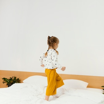 ベッドの上に立っているフルショットの女の子