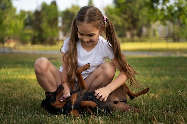 Full shot girl ticking dog