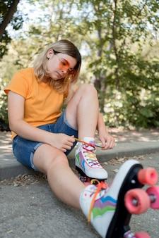 ローラースケートのひもを結ぶフルショットの女の子