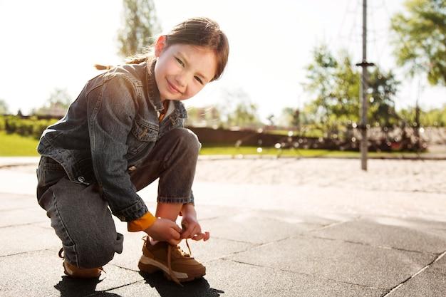 彼女の靴紐を入力するフルショットの女の子