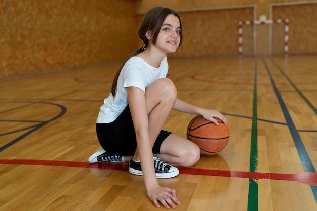 Full shot girl with basket ball at gym