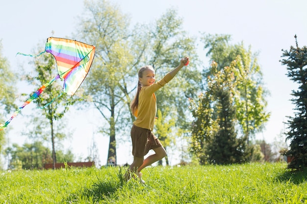 カラフルな凧を持つフルショットの女の子