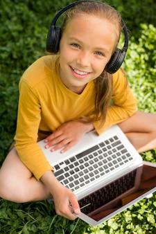 ノートパソコンとヘッドフォンでフルショットの女の子