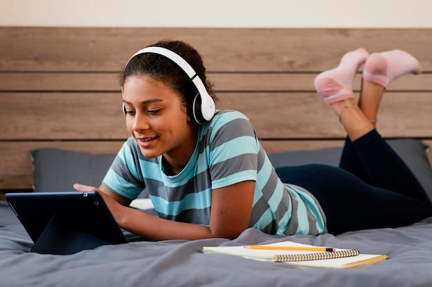 ベッドの中でタブレットとヘッドフォンでフルショットの女の子