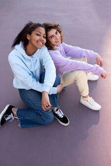屋外に座っているフルショットの女の子