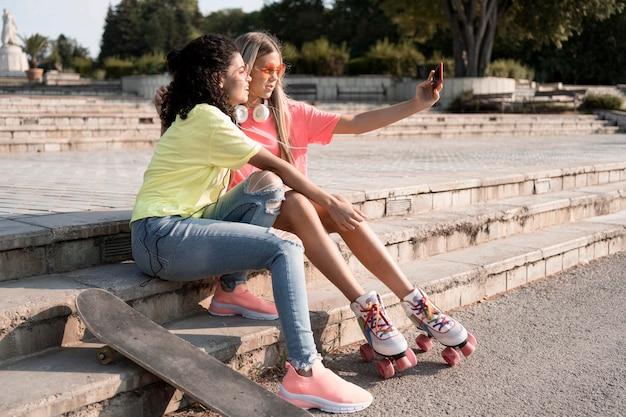 Full shot girls taking selfie together