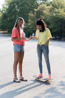 Ragazze del colpo pieno con lo skateboard