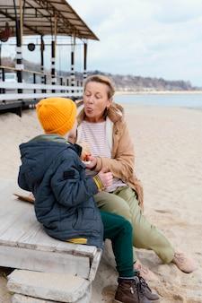 해변에서 풀 샷 할머니와 아이