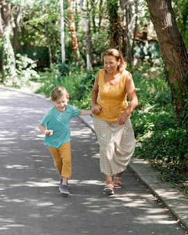 フルショットのおばあちゃんと子供が走っています