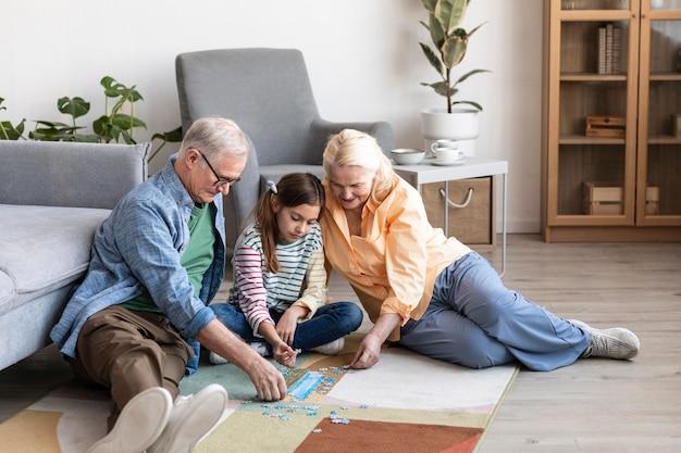 Бабушка и дедушка и ребенок решают головоломку