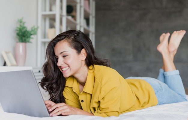 Full shot happy brunette woman with laptop