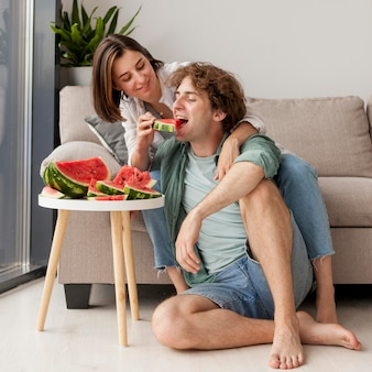 Full shot happy couple eating watermelon
