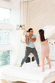 Full shot happy couple fighting with pillows in bed