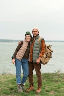 水の近くでポーズをとってフルショット幸せなカップル