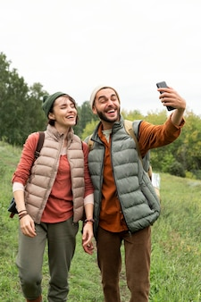 Full shot happy couple taking selfie in nature with smartphone