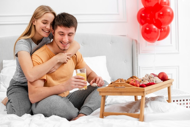 Full shot happy couple with breakfast in bed