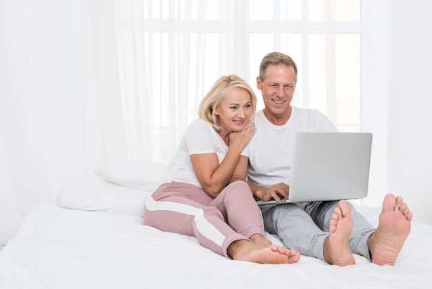 Full shot happy couple with laptop in the bedroom