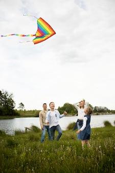 Полный снимок счастливая семья запускает воздушный змей на улице