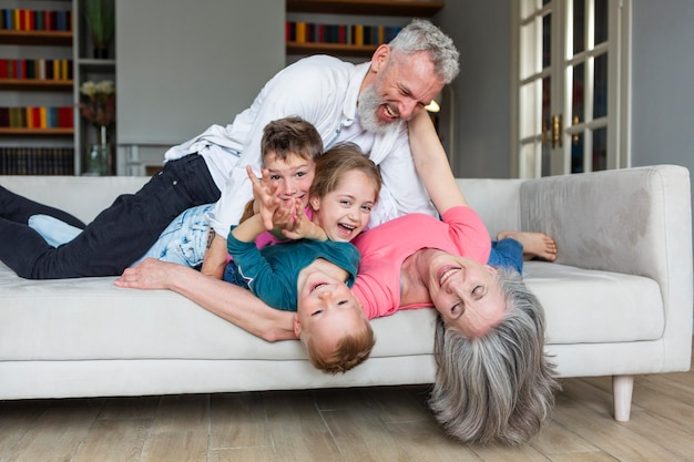Full shot happy family playing on couch