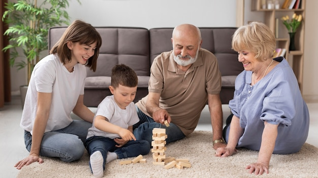 Full shot happy family playing game on floor