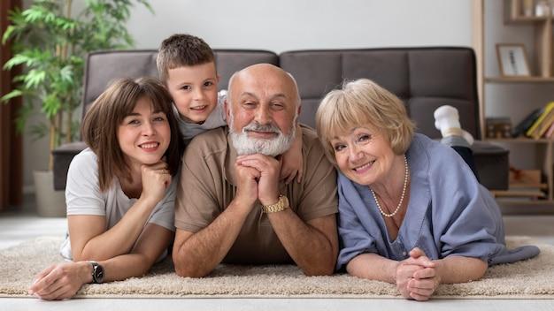 Full shot happy family posing on floor