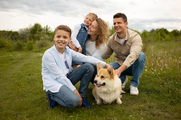 Famiglia felice a tutto campo con un cane adorabile